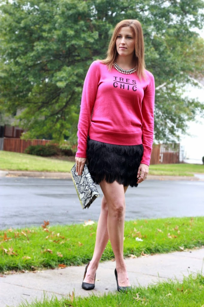 The perfect tres chic sweater paired with a fringe skirt and snakeskin clutch.