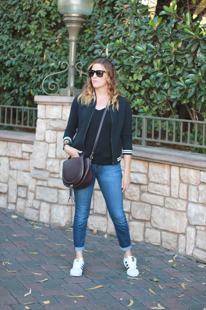 The Fashionista Momma shares a black bomber jacket with jeans and adidias for a casual look at Disneyland.