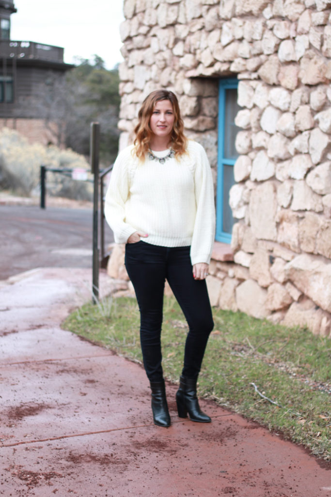 A cozy cream sweater with black jeans.