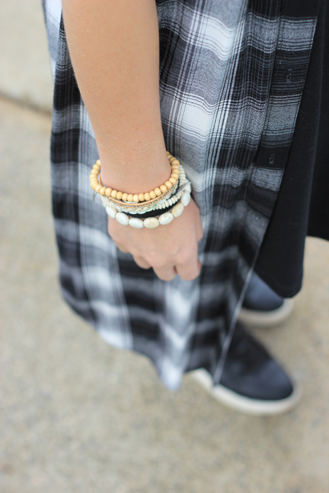 A plaid shirt dress layered over a black dress.