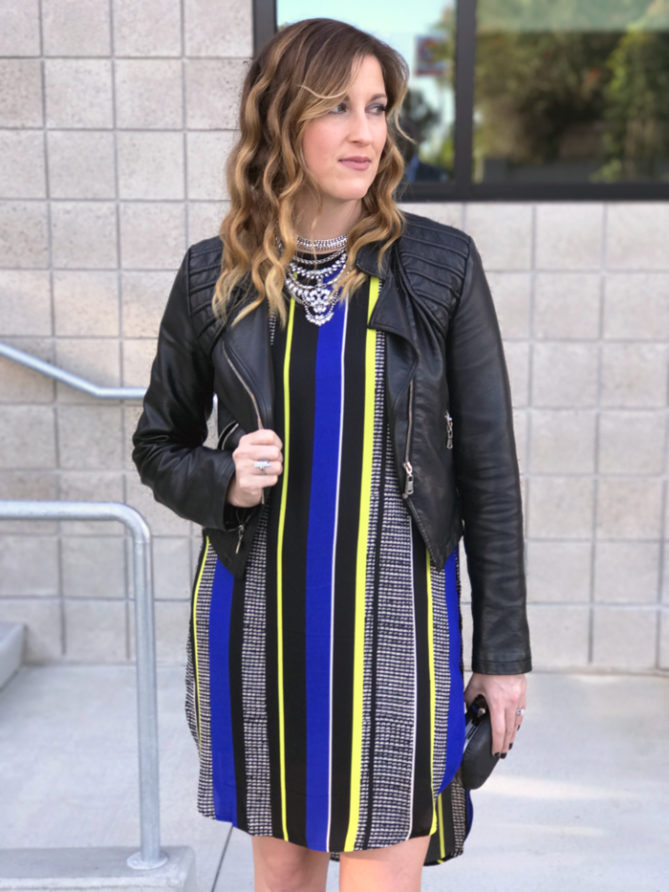 A printed dress paired with a leather jacket and statement necklace.