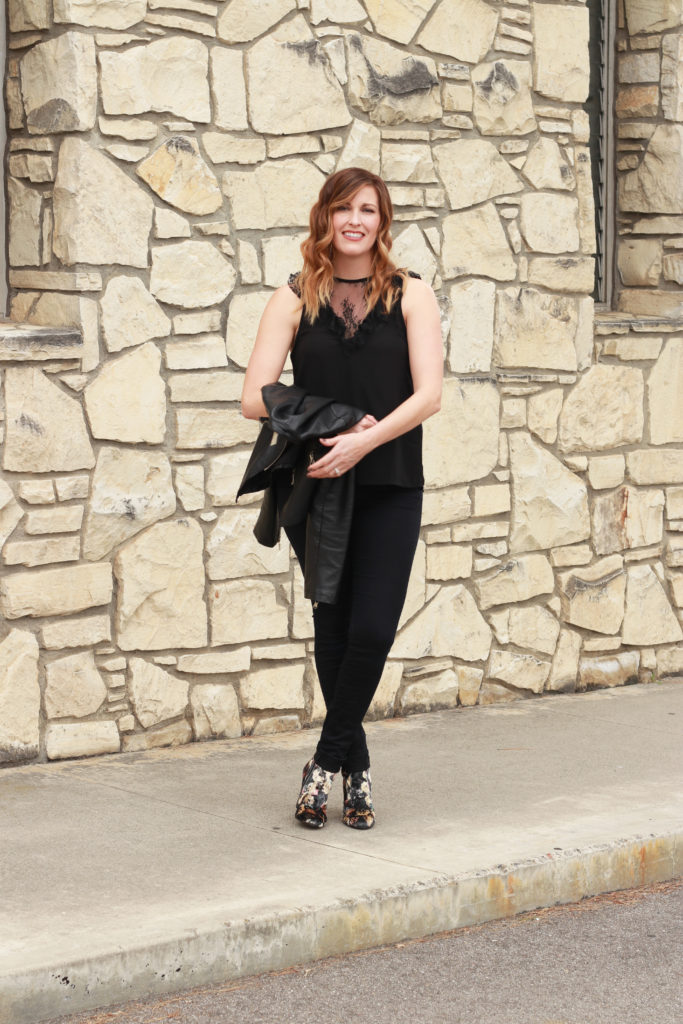 A black lace top with a fringe clutch and floral boot.