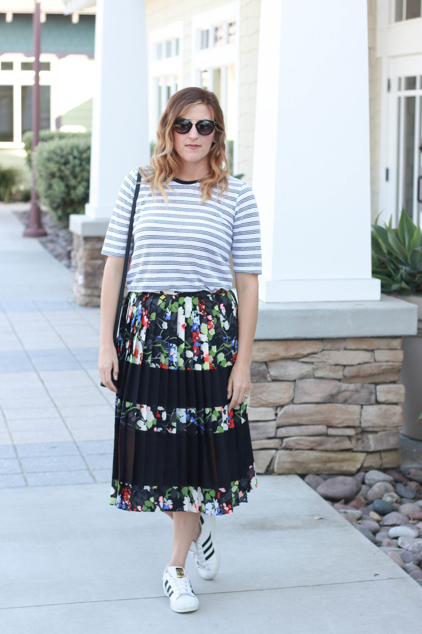 A floral skirt with a striped top and sneakers. A casual spring look.