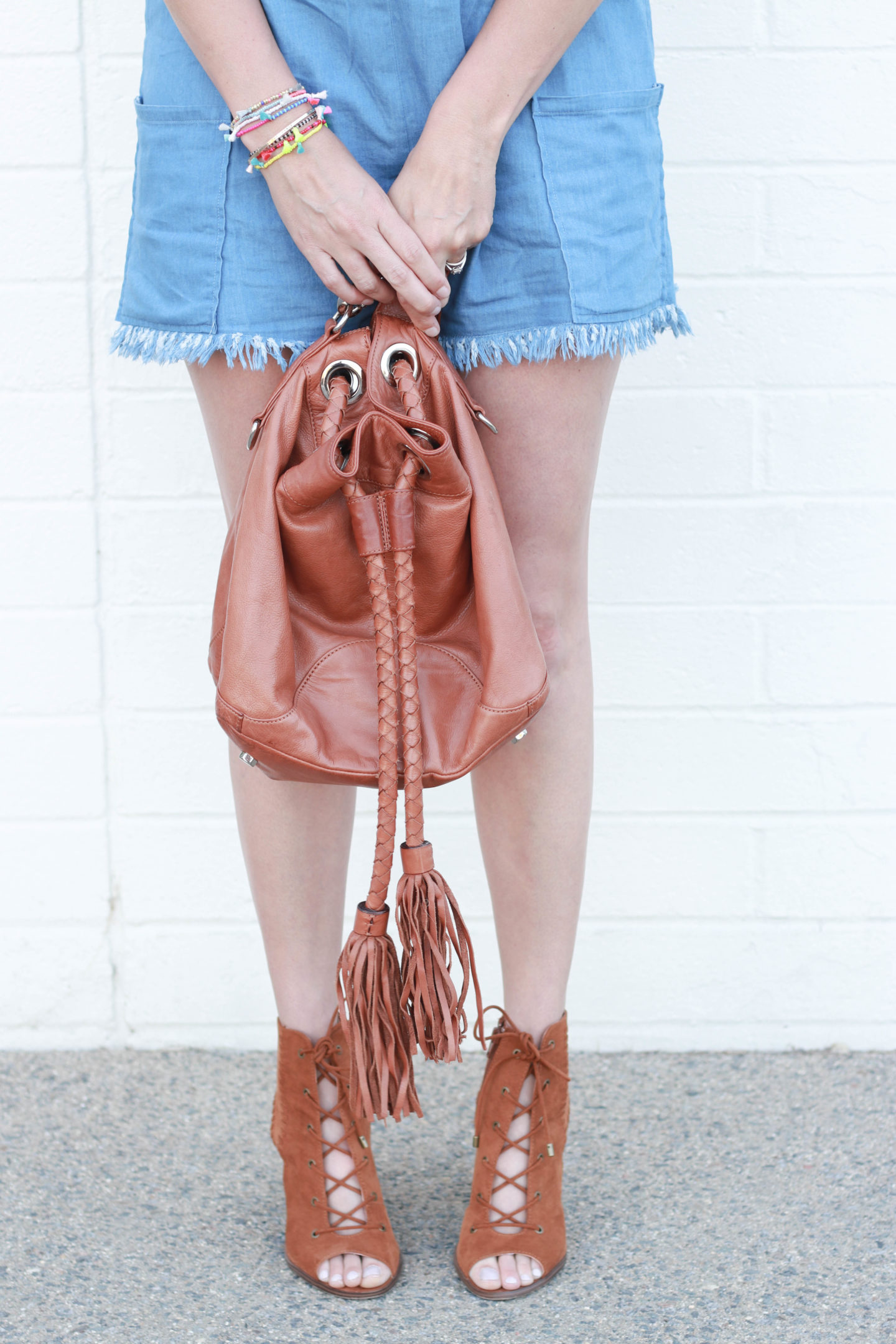 A frayed chambray romper with tassel bracelets and a Rebecca Minkoff bucket bag.