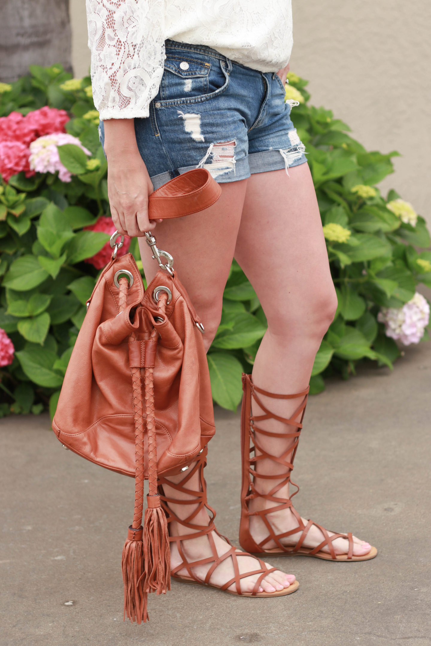 A lace top with gladiator sandals and destroyed denim.