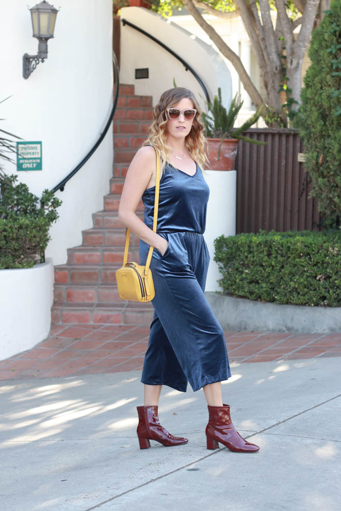 A perfect velvet jumpsuit with red patent leather boots and mustard purse.