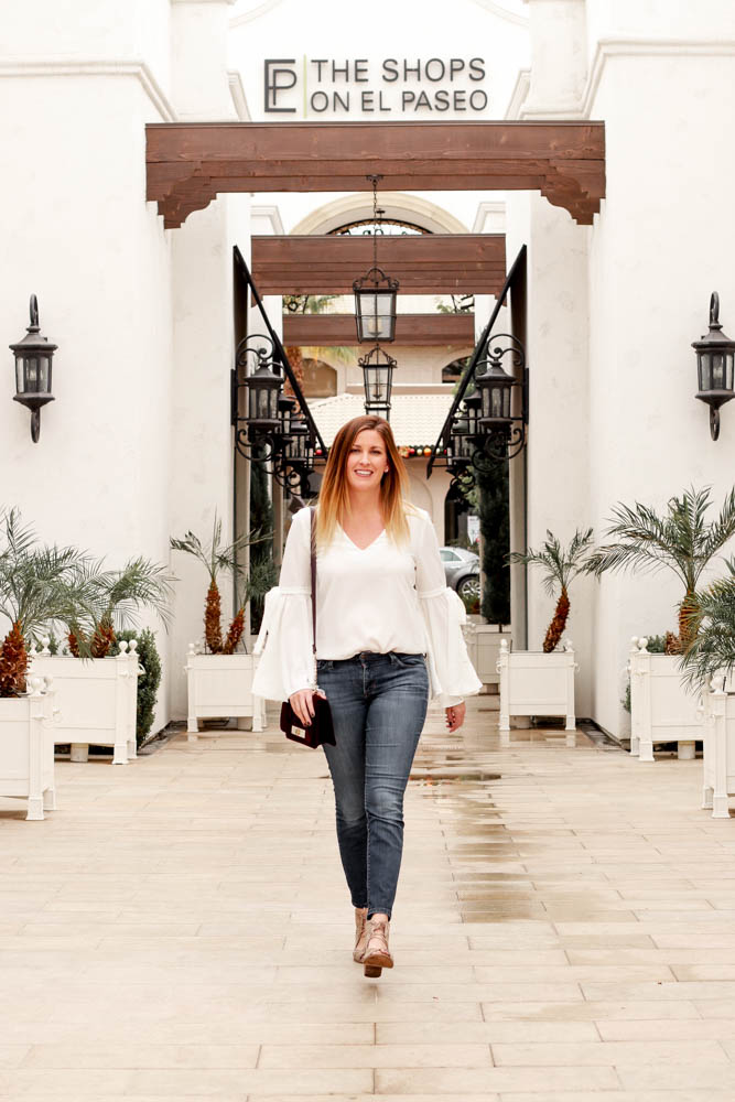 The perfect white bell sleeve top with jeans and a velvet purse. - Spring Break Travel Ideas by popular Los Angeles blogger The Fashionista Momma