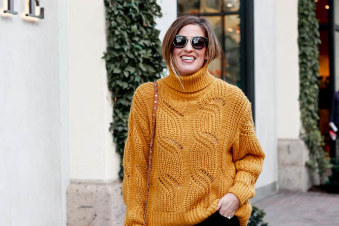 A great winter brunch outfit with a mustard chunky knit sweater and black jeans.