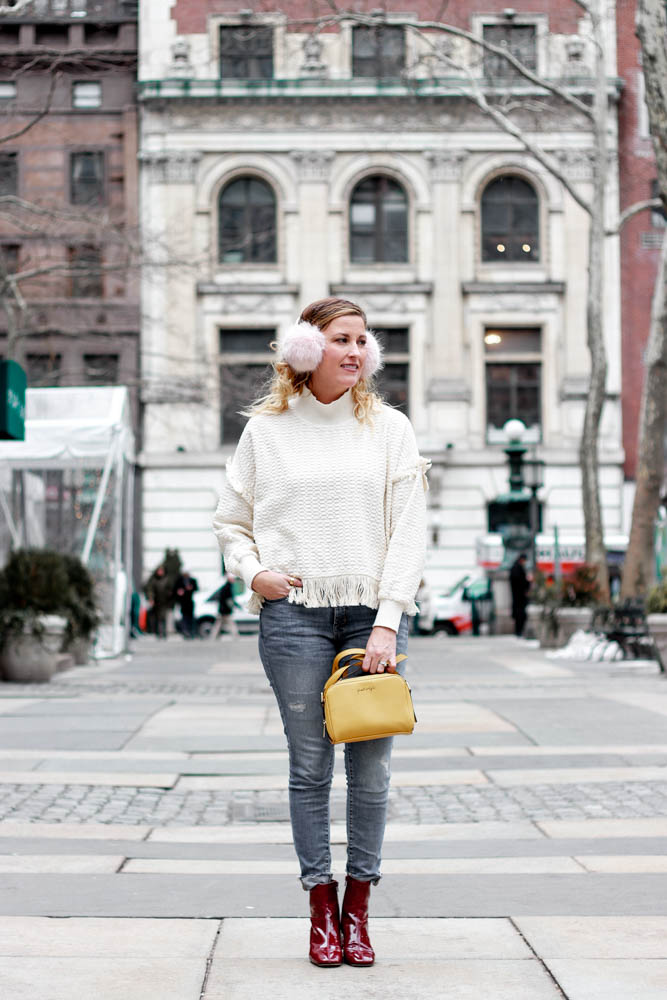 A fringe sweater with patent leather boots and a mustard crossbody bag.