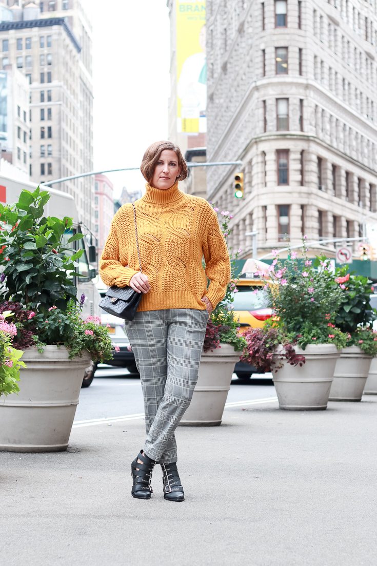 The Fashionista Momma shares the perfect fall look with an oversized sweater, plaid pants and statement boots.