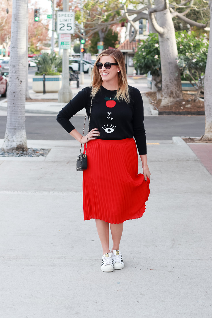 The Fashionista Momma styles a graphic sweater and pleated skirt.