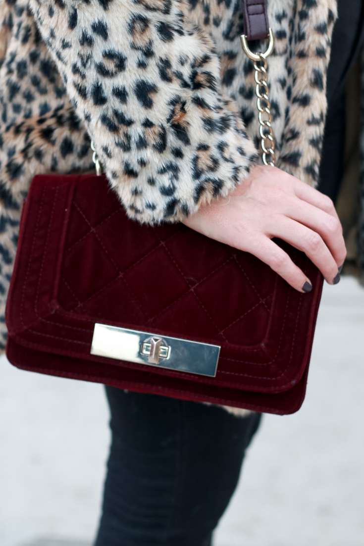The Fashionista Momma shares a leopard print coat, velvet purse and black denim.