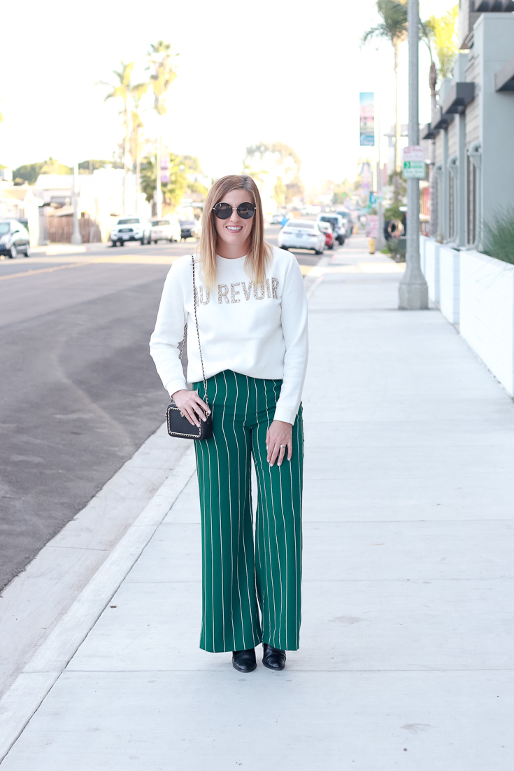 The Fashionista Momma shares wide leg pants and a graphic sweatshirt.