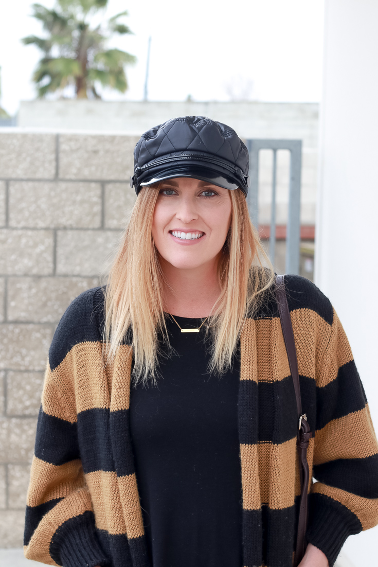 The Fashionista Momma styles a black dress, striped cardigan and black hat.
