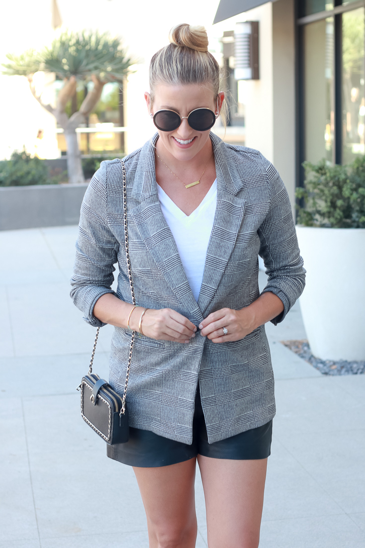 Popular US Style Blogger, The Fashionista Momma, shares a plaid boyfriend blazer with leather shorts. Woman wearing plaid blazer.