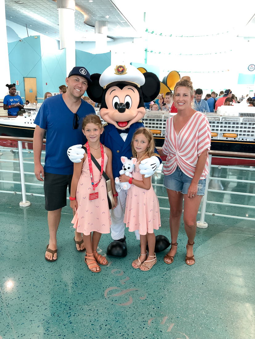 The Ultimate Disney Cruise Guide featured by Top US travel blog, The Fashionista Momma; family posing with Mickey Mouse