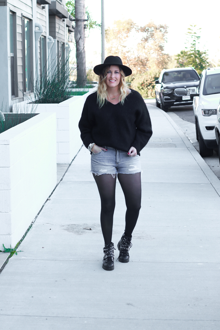 How to Style Your Summer Shorts In The Winter featured by Top US Style Blog, The Fashionista Momma; blonde woman wearing Target Denim shorts, black tights and Zara boots.