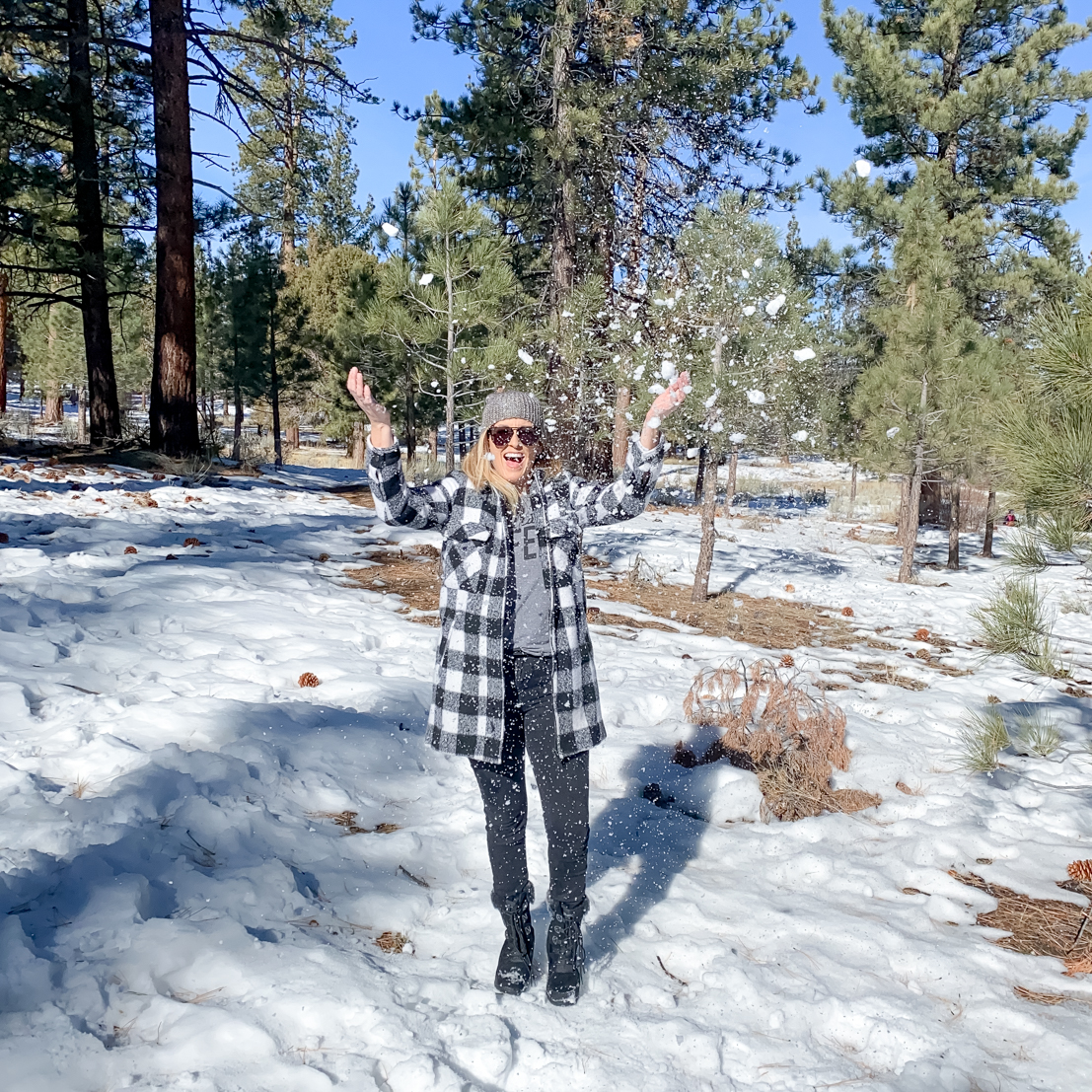 The Ultimate trip to Big Bear featured by Popular US Travel Blog, The Fashionista Momma; Woman throwing snow in plaid jacket