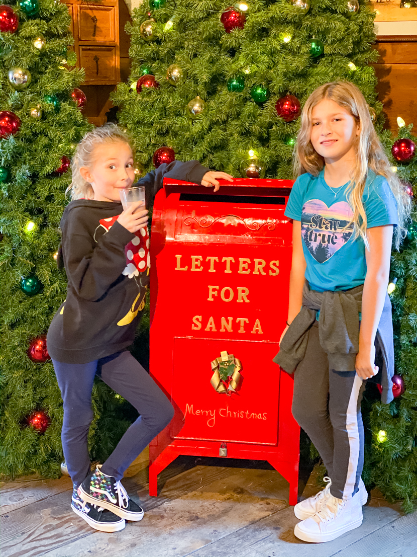 The Ultimate SoCal Staycation featured by Popular US Travel Blog, The Fashionista Momma; 2 girls at Knott's Berry Farm delivering letters to Santa
