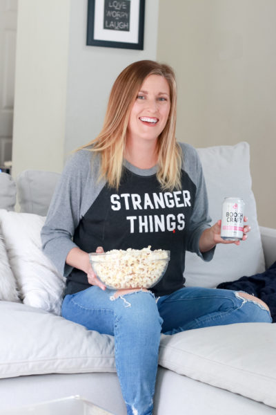 Binge Worthy Shows featured by popular mom lifestyle blogger, The Fashionista Momma; woman watching TV with popcorn and Boochcraft.