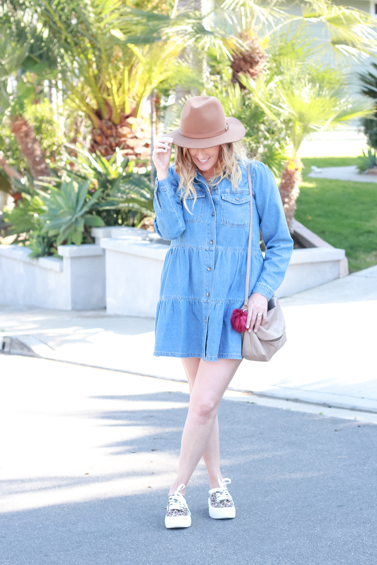 Free People Denim Dress styled by popular US Style Blogger, The Fashionista Momma; woman in denim dress with sneakers and a hat.