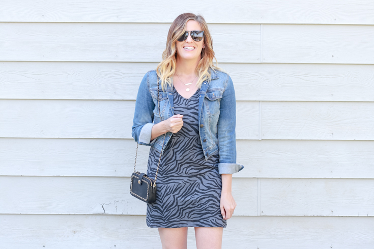 A Zebra Printed Dress featured by popular US Style Blogger, The Fashionista Momma; woman wearing a zebra print dress with converse and a denim jacket.