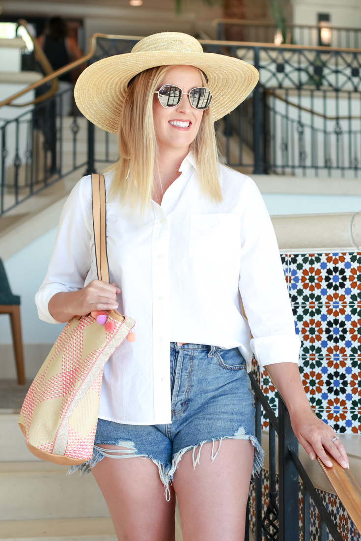Cutoff Shorts And A Button Down featured by Popular US Style Blogger, The Fashionista Momma; woman wearing shorts with a white button down and clear sandals.