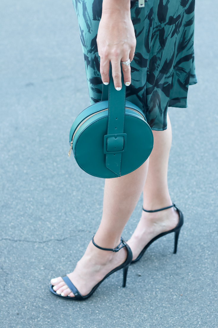 A printed silk midi dress featured by popular US Style Blogger, The Fashionista Momma; green circle handbag