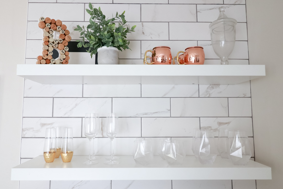 Popular US Style Blogger, The Fashionista Momma, shares the perfect DIY Custom Bar Area with a waterfall edge butcher block countertop; decorated floating bar shelves.