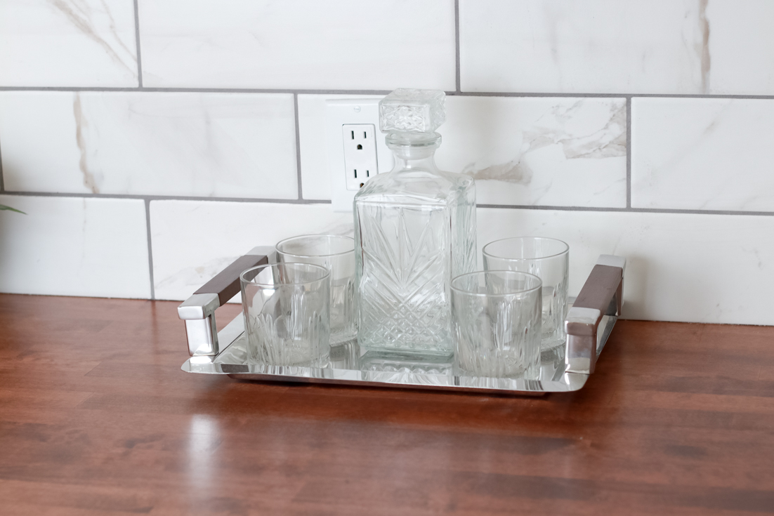 Popular US Style Blogger, The Fashionista Momma, shares the perfect DIY Custom Bar Area with a waterfall edge butcher block countertop; silver platter with whiskey set.