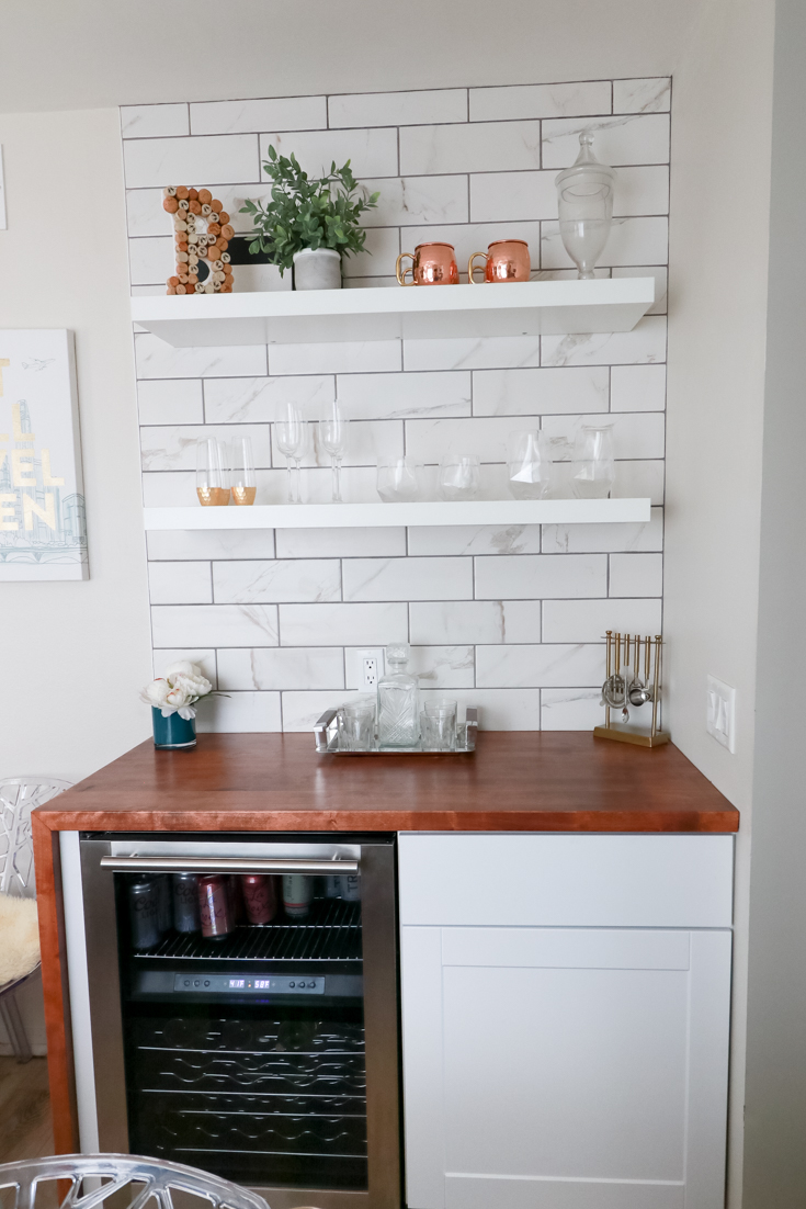 Popular US Style Blogger, The Fashionista Momma, shares the perfect DIY Custom Bar Area with a waterfall edge butcher block countertop; bar area with floating shelves