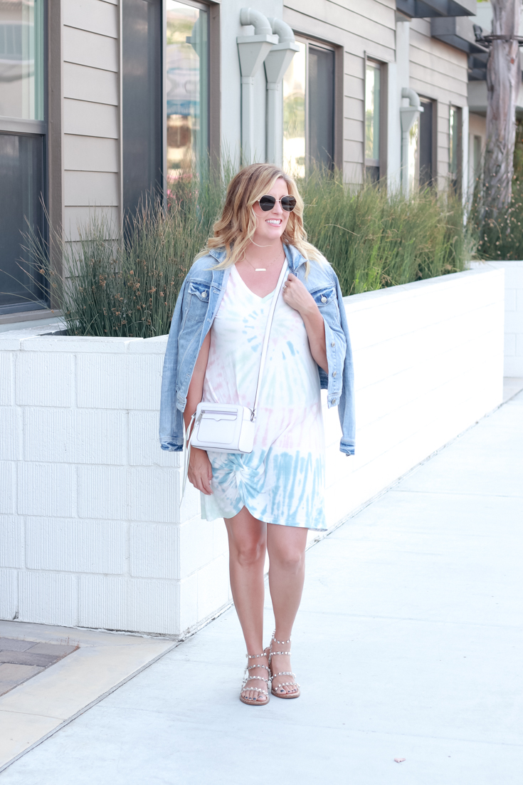 How To Wear Tie Dye In Your 30's featured by popular US Style Blogger, The Fashionista Momma; woman wearing cutoff shorts and tie dye sweater.
