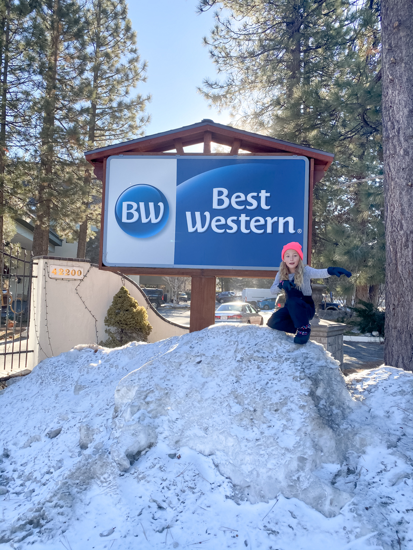 Best Tips To Road Trip With Kids featured by popular US family travel blogger, The Fashionista Momma; kid in front of best western hotel in big bear.