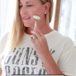 Must Have Beauty Tools featured by Popular US Beauty Blogger, The Fashionista Momma; woman using a jade roller with eye pads on.